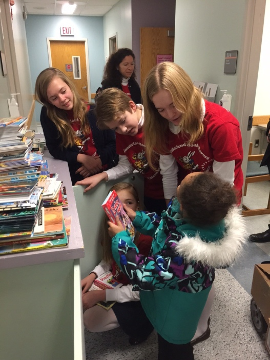 a little girl selects one of our donated books at the hospital